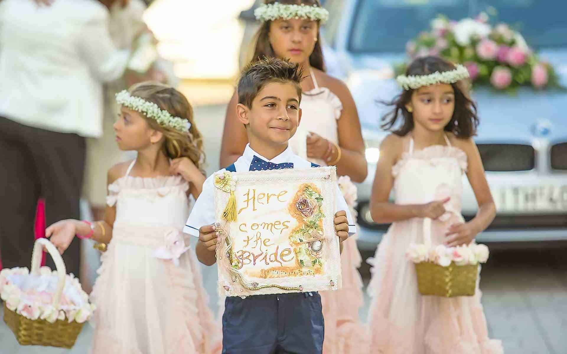 Sweet-Innocence-Ring-Bearer-Boasting-A-Here-Comes-The-Bride-Sign-Flower-Girls-To-Enchant-The-Way-With-Rose-Petals