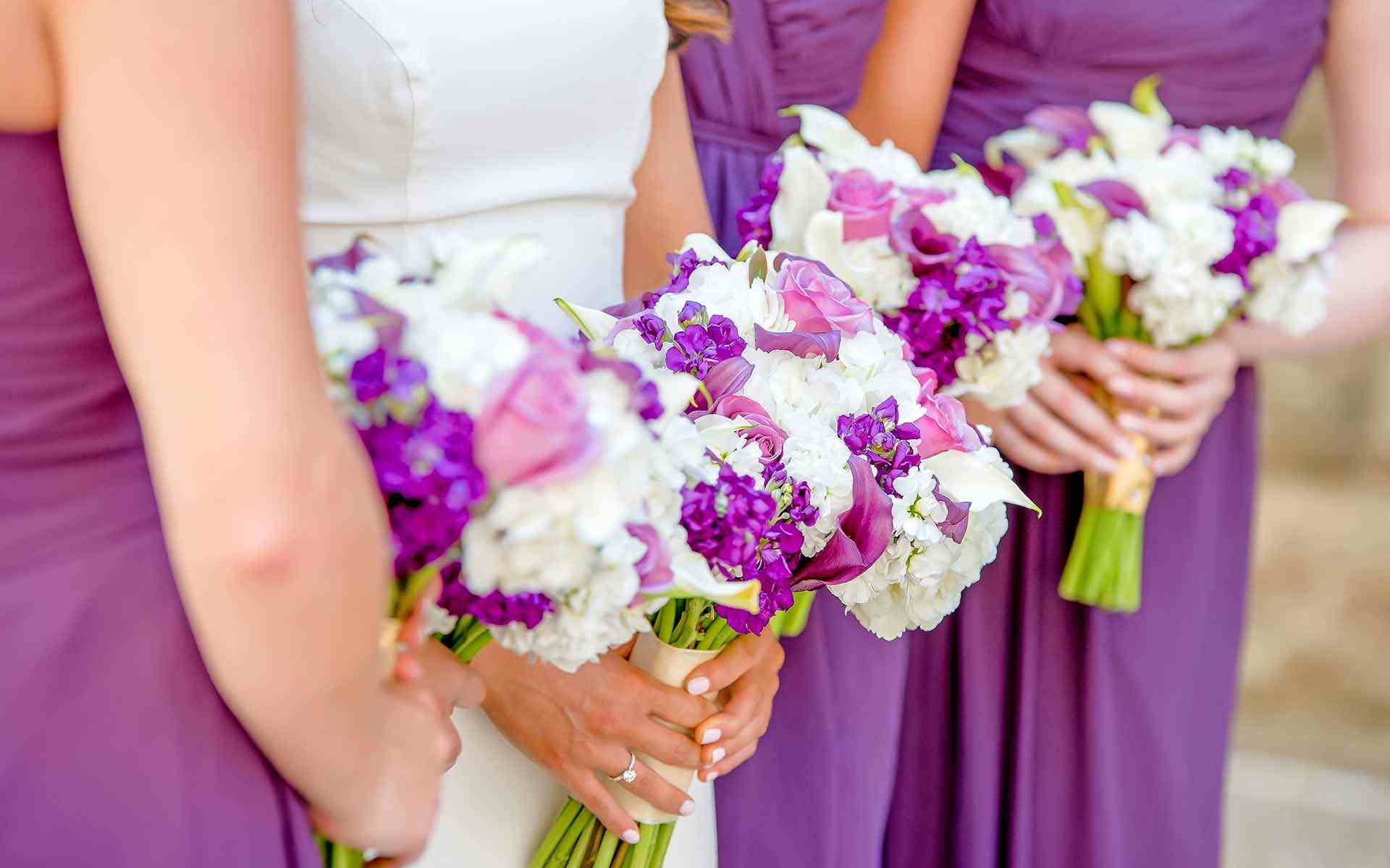 The-Bride-Among-The-Bridesmaids-With-Bouquets-Full-Of-Purple-And-White-Blooms-Popped