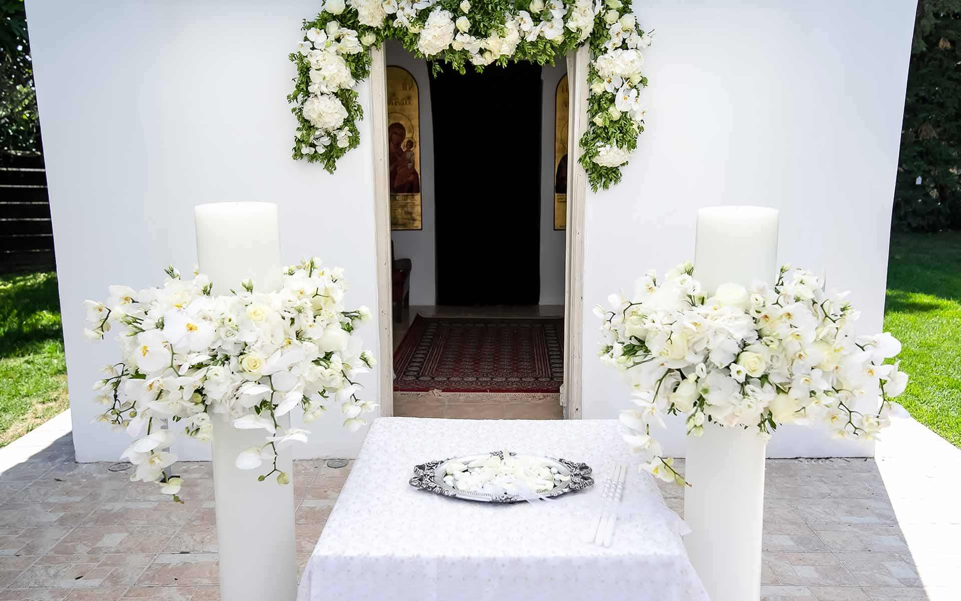 Unity-candle-set-with-Orchids-hydrangeas-and-roses-all-in-white-for-an-Orthodox-ceremony