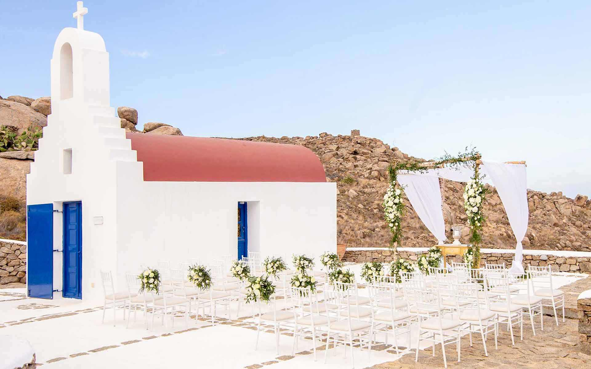 White-seats-on-the-outside-of-a-monastery-on-an-island-of-the-Cyclades-who-are-waiting-for-the-guests-of-the-wedding-ceremony