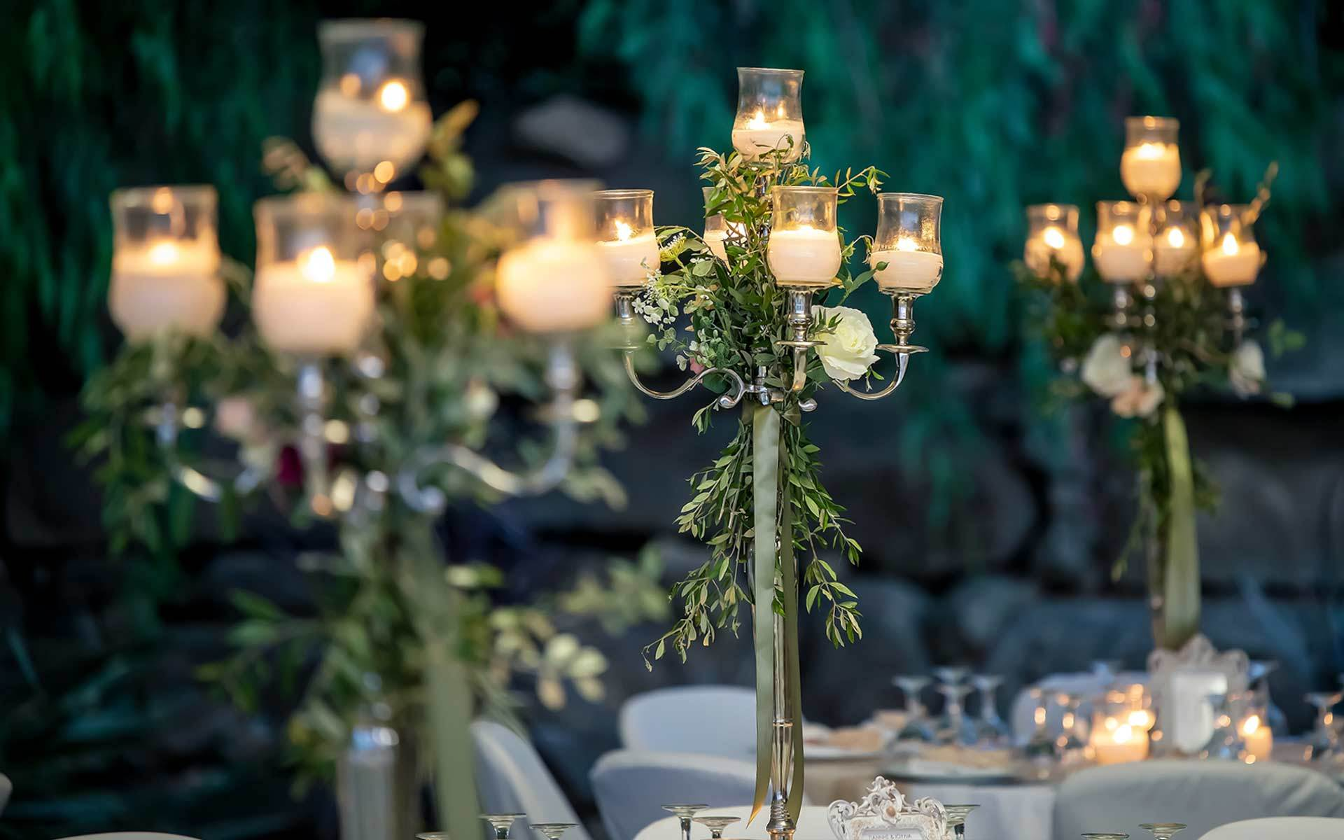 Rustic-wedding-table-decor-with-candelabras-with-olive-leaf-garland-roses-green-ribbons