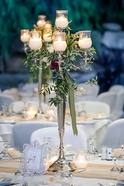 Rustic-wedding-table-decoration-with-tall-candelabras-with-olive-leaf,-garland,-roses-&-green-ribbons