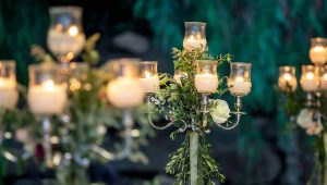 Rustic-wedding-table-decor-with-candelabras-with-olive-leaf,-garland,-roses-&-green-ribbons